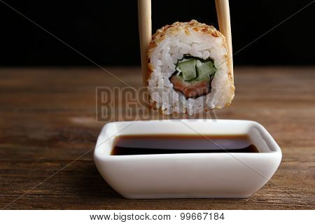 Dipping roll in sauce on dark background