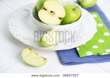 Green apples in saucer on table with napkins, closeup