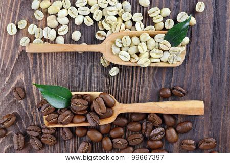 Green and brown coffee beans with spoons on wooden table close up