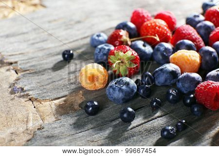 Heap of sweet tasty berries on wooden table close up
