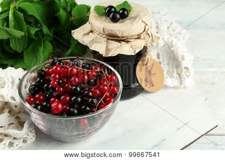 Ripe forest berries in glass bowl on light background