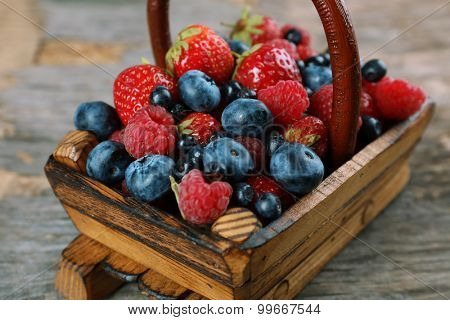 Sweet tasty berries in basket on wooden table close up