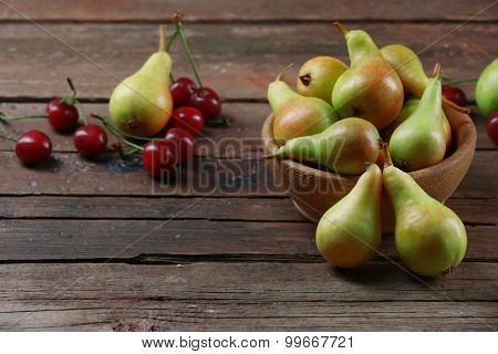 Ripe pears and cherries on wooden table close up