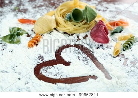 Row pasta on flour background