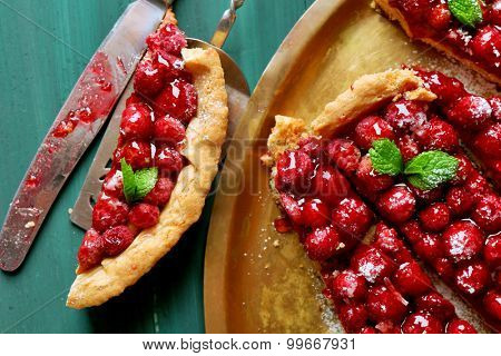 Piece of tart with raspberries on tray, close-up, on color wooden background