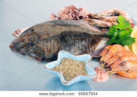 Fresh fishes and shrimps with spices  on metal background