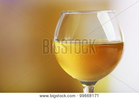 Glass of wine on light blurred background