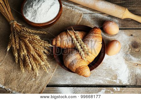 Fresh croissants with flour on wooden table, top view