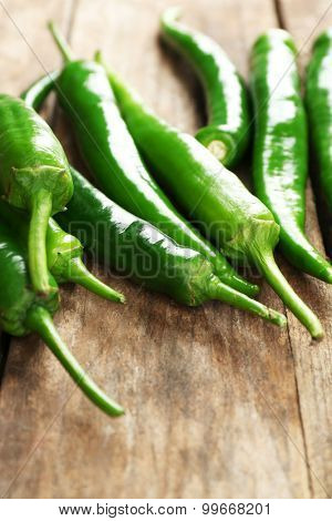 Green hot peppers on wooden table close up