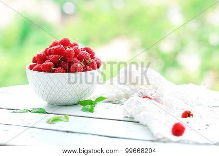 Fresh raspberries in bowl on wooden table on blurred nature background