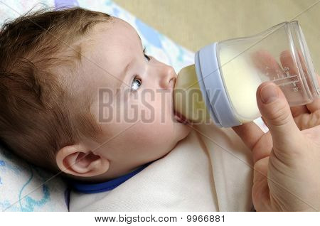 Close Up Of A Baby Girl Drinking Milk From Plastic Bottle