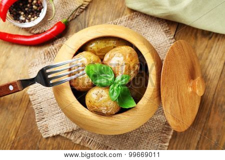 Baked potatoes in bowl on wooden table, top view
