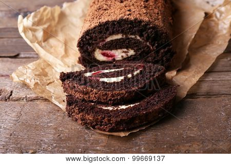 Chocolate roll with cream and berries on table close up