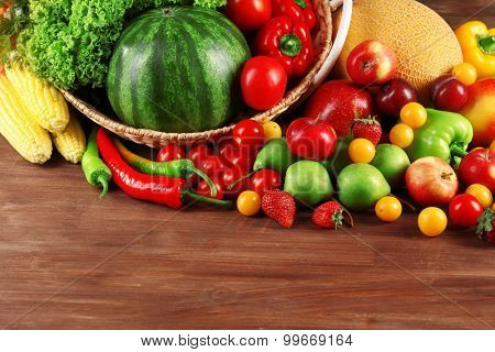 Composition with fresh fruits and vegetables on wooden background