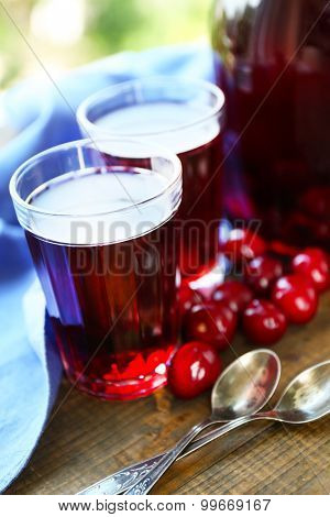 Sweet homemade cherry compote on table on wooden table, on bright background