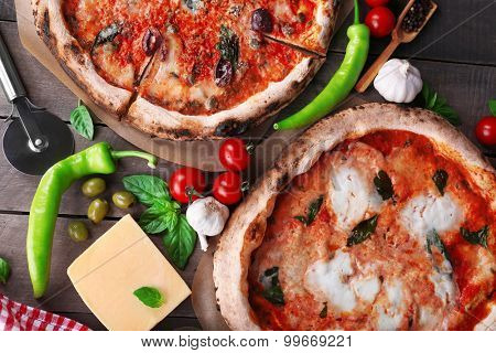 Delicious pizzas on wooden table, top view