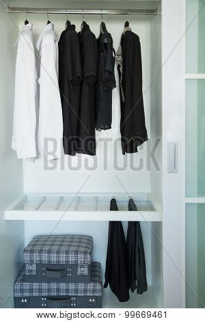 Clothes hang on a shelf in a designer clothes store, modern closet with row of cloths hanging