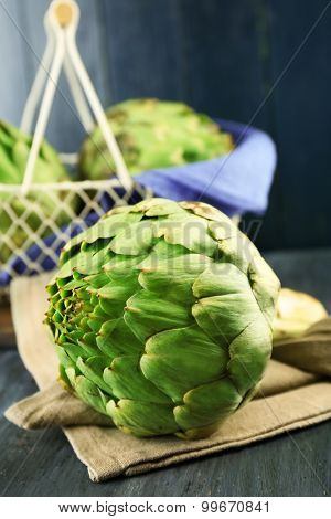 Artichokes  in basket on color wooden background
