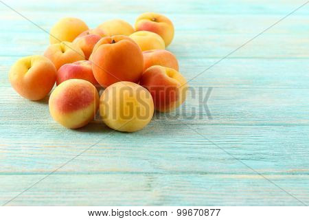 Ripe apricots on wooden table close up