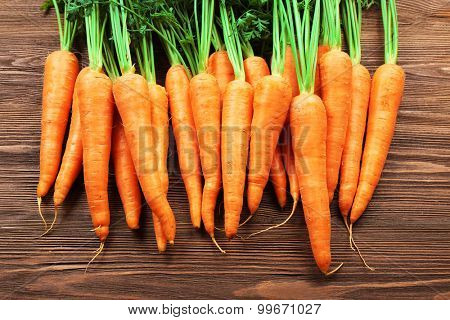 Fresh organic carrots on wooden table, closeup