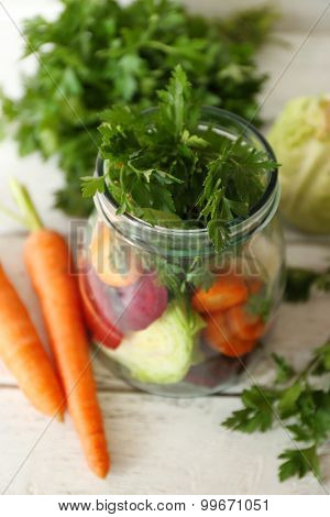 Fresh vegetables in glass bottle on wooden table, closeup