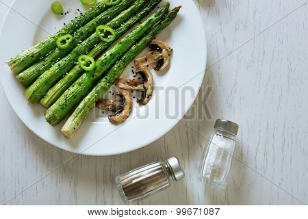 Roasted asparagus on plate on table background
