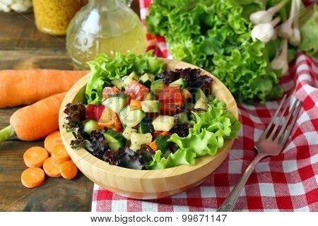 Wooden bowl of fresh vegetable salad on table, closeup
