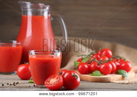 Full jug and glasses of tomato juice with vegetables on wooden table close up