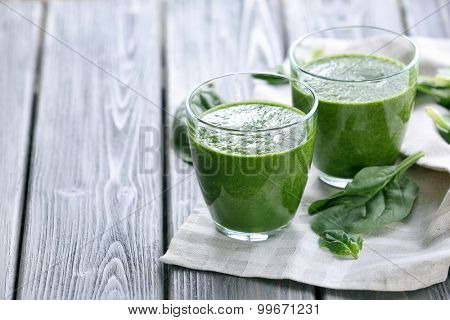 Glasses of spinach juice with napkin on wooden background