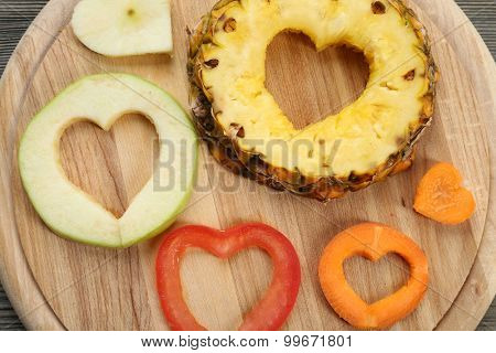 Fruits slices with cut in shape of heart on wooden background
