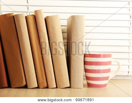 Books and cup on wooden windowsill, closeup