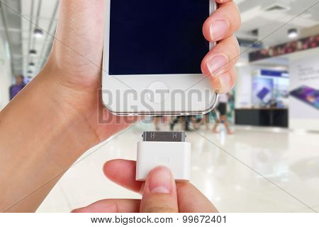 Female holding USB port charger wrong connect to smart phone.
