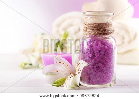 Spa treatment and flowers on wooden table, on light background