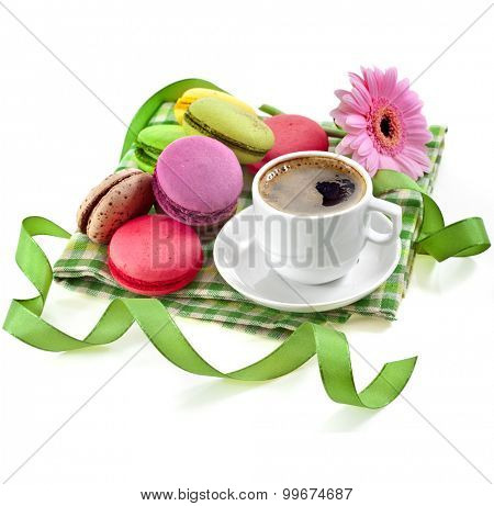 coffee cup with colorful macaroons in a table serviette isolated on a white background