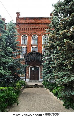 Elets, Russia - June 12, 2015: Day of Russia,Alley With Tall Fur Trees Leading To Old Red Brick Hous