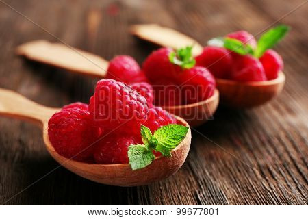 Fresh red raspberries in spoons on wooden table, closeup