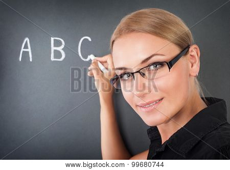 Closeup portrait of beautiful young teacher writing on blackboard letters, cute educator in elementary school, start of educational season