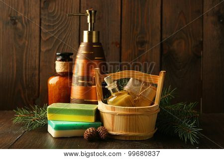 Essential oil of pine, handmade soap in wooden bucket and spa treatments on wooden background