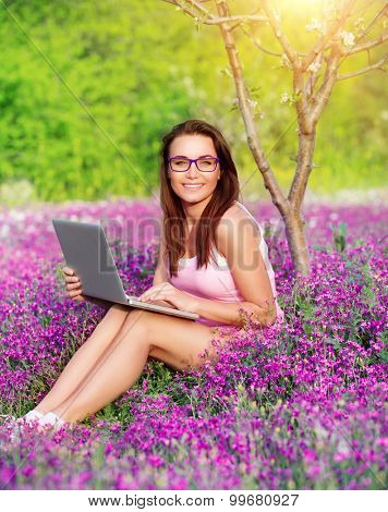 Student girl in the garden, working on laptop in beautiful fresh garden on flowers field, studying in university, enjoying educational period
