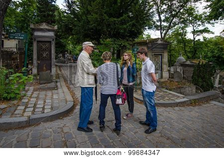 Volunteer assists tourists with directions at the Pere Lachaise Cemetery