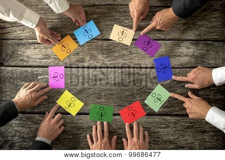 Successful Business Leaders Creating Diverse And Competent Business Team Seated Around A Wooden Tabl