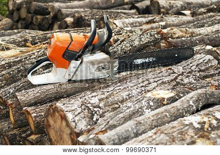 Gasoline Powered  Chainsaw On Pile Of Cut Wood