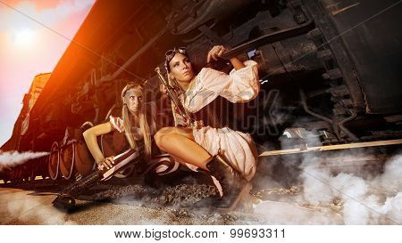 Two Sexy Woman In The Steam-punk Clothes Are Hiding Beneath The Vintage Train.