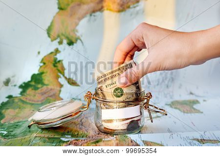 Collecting Money For Travel. Glass Tin As Moneybox With Cash Savings (banknotes And Coins) On Map