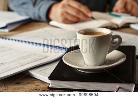 In the foreground is a cup of coffee on the diary for records closeup