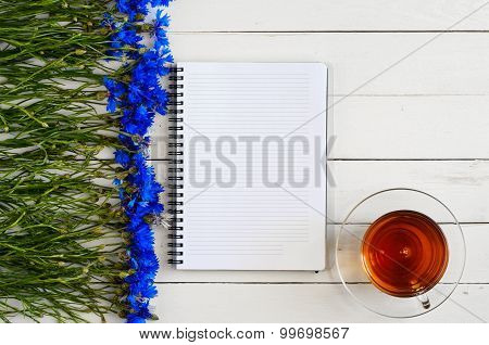 White open notebook for notes on a white wooden table with a bouquet of blue flowers