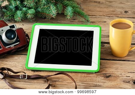 White tablet computer with a blank screen, a cup of coffee, a branch of spruce and vintage camera