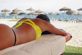 picture of woman g-string  - Massage area on the beach with suntanned beautiful woman lying down on summer vacation season - JPG