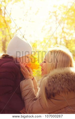 Happy mother holding her daughter's face in hands and smiling to her, happy childhood, mother's love, sunny backlight in autumn park.