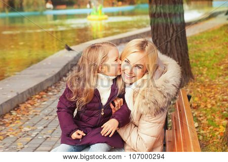 Happy smiling mother with daughter have a rest sitting in autumn park on a bench near lake, dauther give a kiss to her mother.